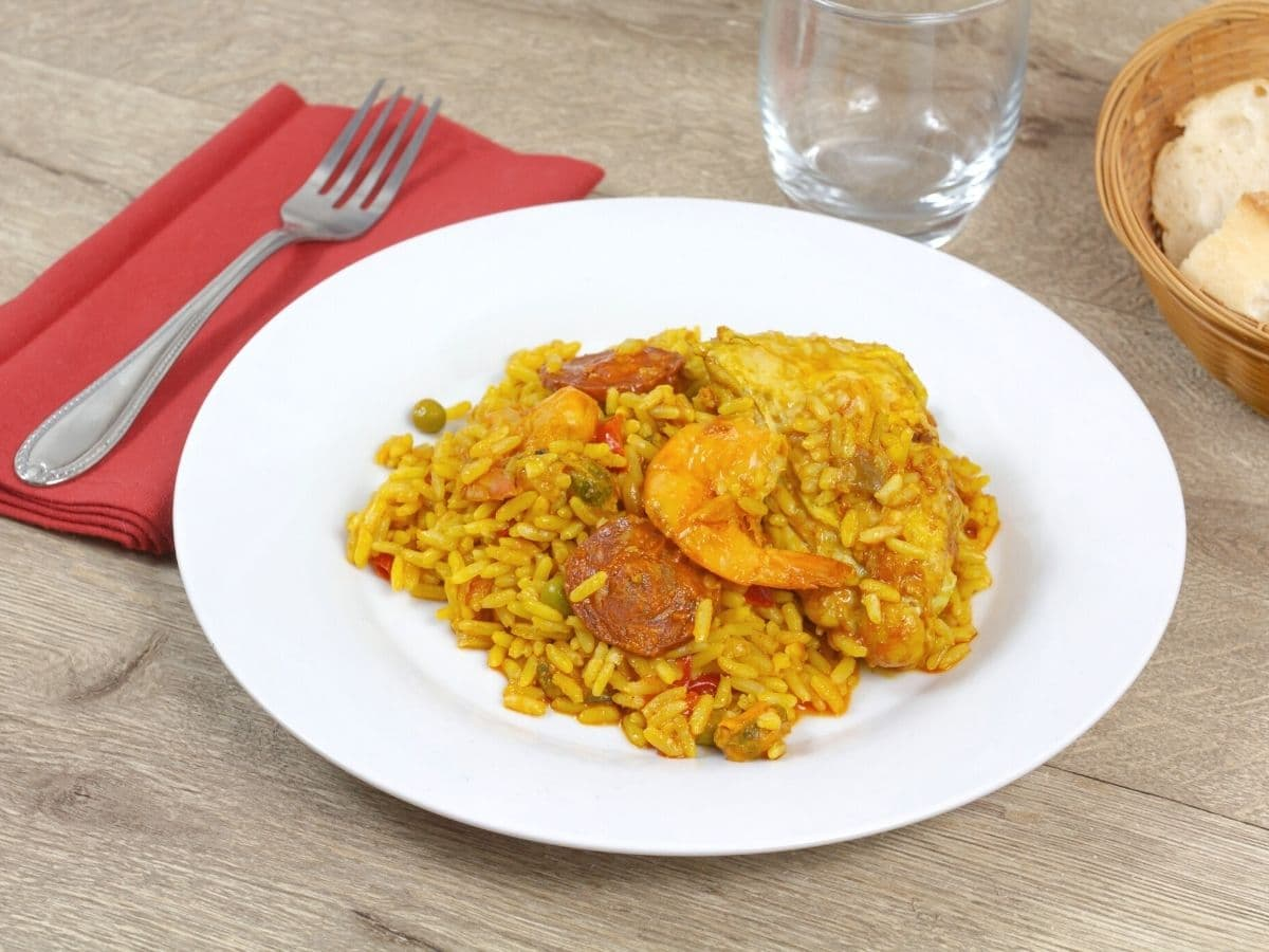 a plate of paella on the dinner table