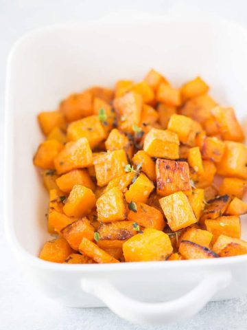 a white baking dish with roasted butternut squash